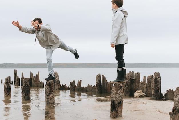 Ojciec i syn mają świetną zabawę i robią ćwiczenia joga w deszczu koło morza