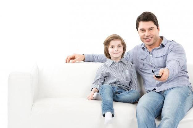 Ojciec i syn na kanapie zmieniają kanały