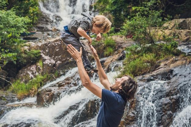 Ojciec i syn na powierzchni pięknego kaskadowego wodospadu datanla w górskim miasteczku dalat w wietnamie