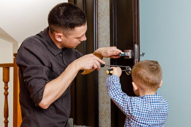 Ojciec i syn naprawiają drzwi. napraw sam dom