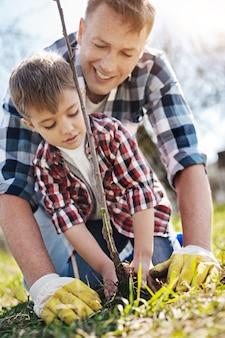Ojciec i syn, oboje w kraciastych koszulach, stojąc na kolanach i sadząc jabłoń