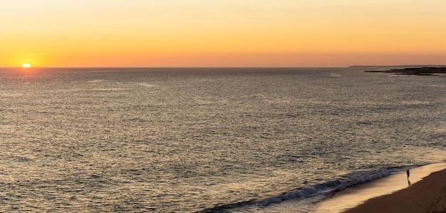 Ojciec i syn oglądają zachód słońca na brzegu morza, na plaży.