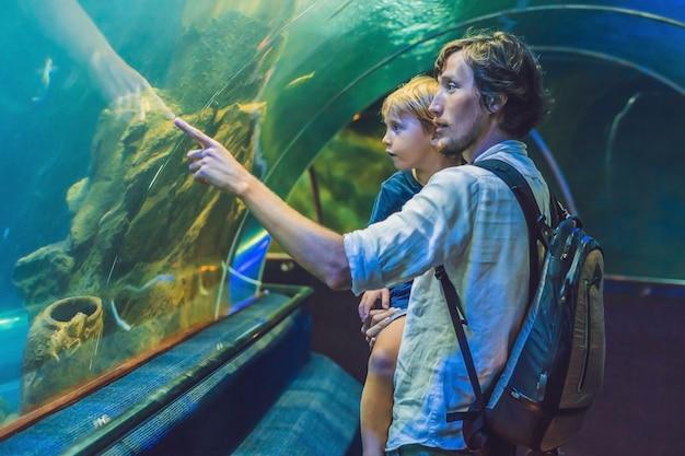 Ojciec i syn patrzą na ryby w akwarium w oceanarium.