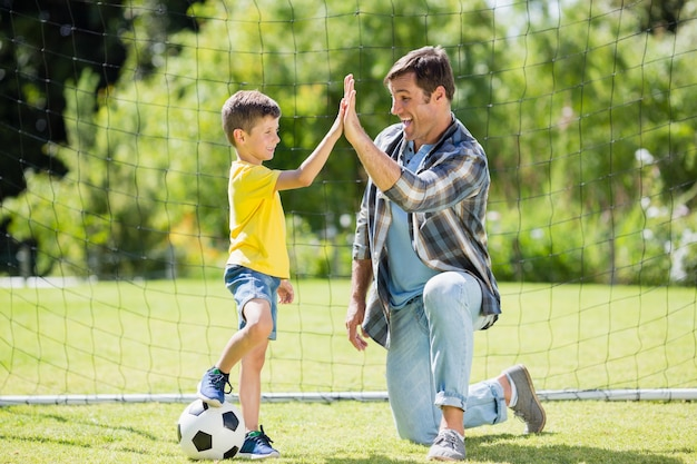 Ojciec i syn przybijają piątkę w parku