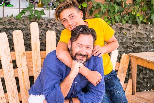 Ojciec i syn przytulają się i cieszą razem słonecznym dniem