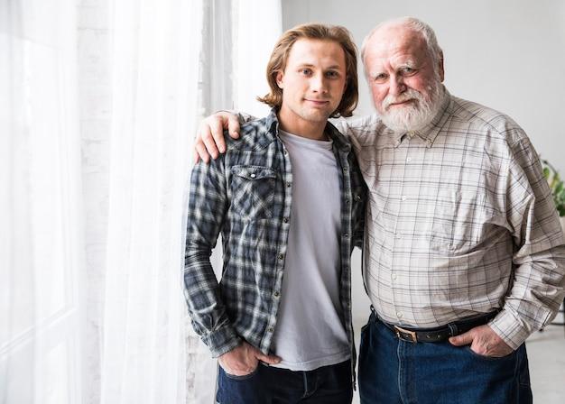 Ojciec i syn przytulanie stojąc w domu