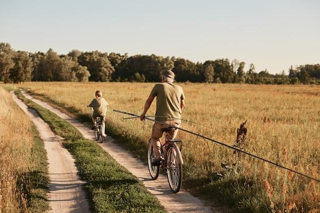 Ojciec i syn razem jeżdżący na rowerach ścieżką w terenie, wędrując z wędkami, chcą łowić ryby, spędzając słoneczny dzień na aktywnym wypoczynku.
