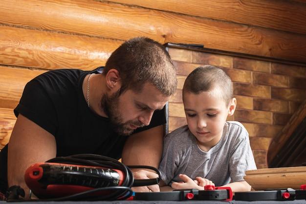 Ojciec i syn razem wykonują drewnianą ptaszarnię w warsztacie