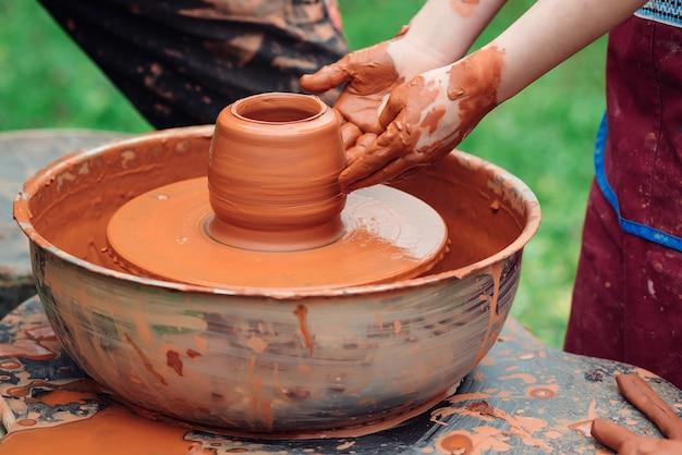 Ojciec i syn robi ceramiczny garnek. rodzina pracuje na kole garncarskim. garncarzy i dłonie dziecka. warsztaty garncarskie na zewnątrz. mistrz uczy dziecko tworzenia na kole garncarskim. ręce i dziecko rzemieślnika