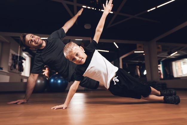 Ojciec i syn robi ćwiczenia prasowe na siłowni.