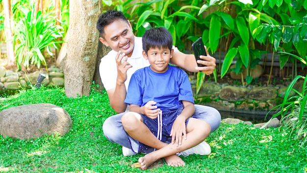 Ojciec i syn robią sobie selfie w parku
