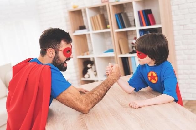 Ojciec i syn rywalizują w siłowaniu się na rękę.
