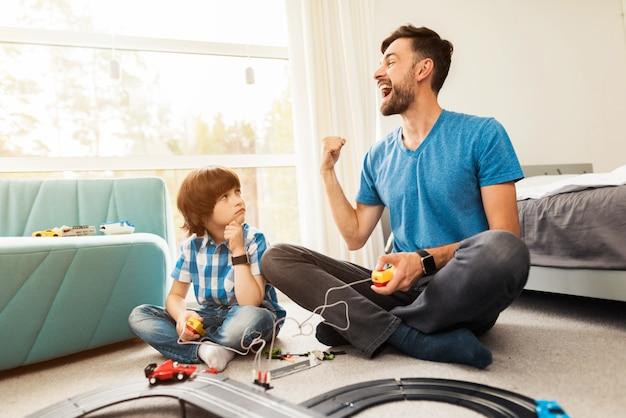 Ojciec i syn rywalizują w wyścigach samochodami dziecięcymi.