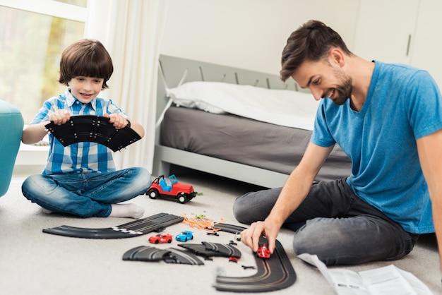 Ojciec i syn rywalizują w wyścigach z samochodami dla dzieci.