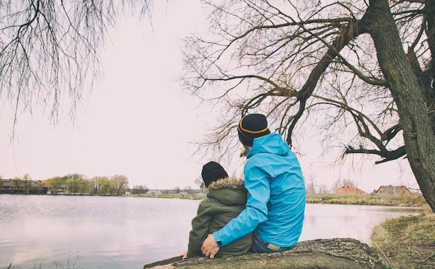 Ojciec i syn siedzą na pniu w pobliżu jeziora i razem się relaksują