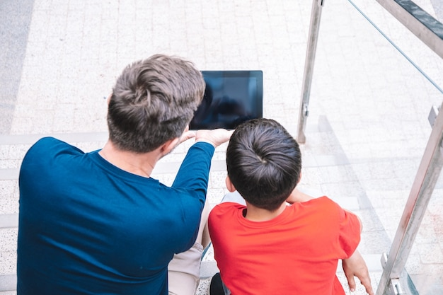 Ojciec i syn siedzą na schodach budynku ofcity i razem oglądają tablet. pojęcie technologii. nowoczesny styl życia. zdjęcie wysokiej jakości
