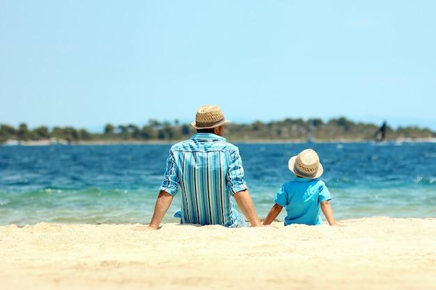Ojciec i syn siedzą nad morzem i śnią, myśląc