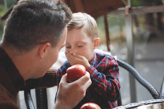 Ojciec i syn siedzą przy stoliku w kawiarni. chłopiec nie chce zjeść jabłka. miłość rodzicielska, szczęśliwe dzieciństwo, opieka nad dzieckiem.