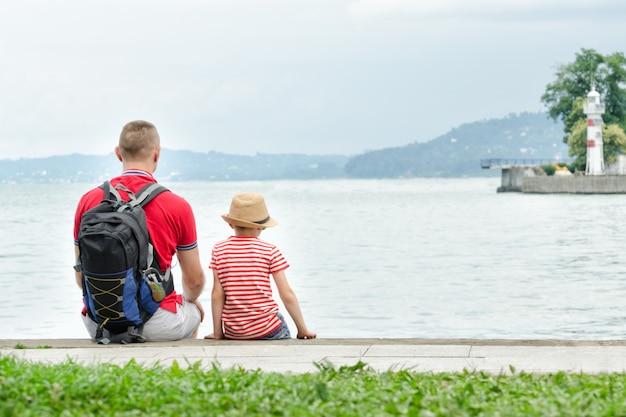 Ojciec i syn siedzi na molo. w oddali morze, latarnia morska i góry. widok z tyłu
