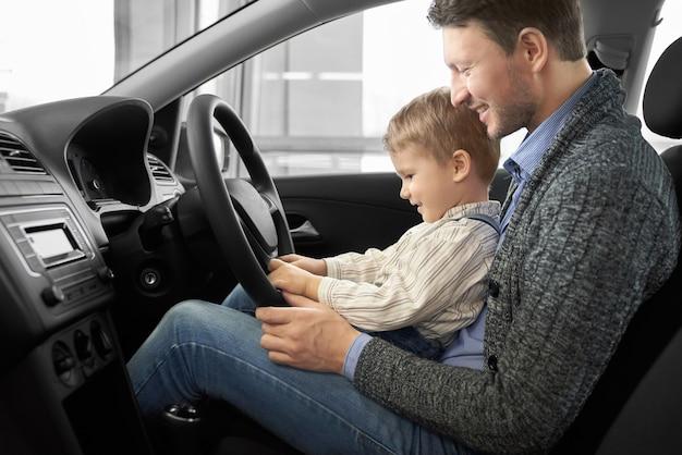 Ojciec i syn siedzi na siedzeniu kierowcy w nowym samochodzie.