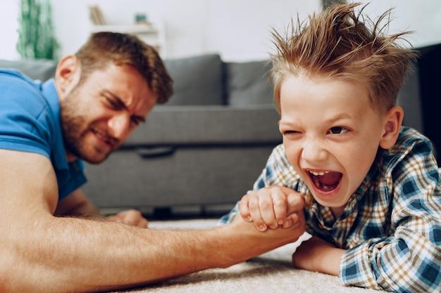 Ojciec i syn siłowanie się na rękę na dywanie w domu clsoe up