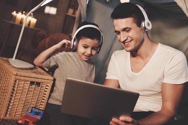 Ojciec i syn słuchają muzyki na laptopie w nocy w domu.