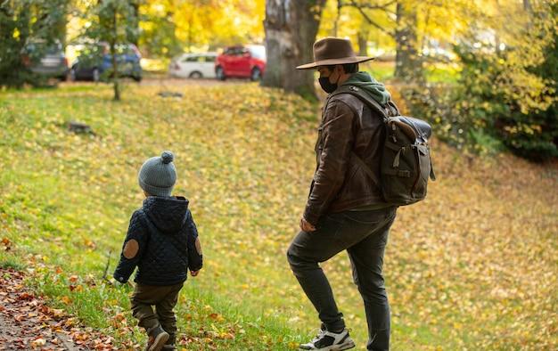 Ojciec i syn spacerują po parku jesienią