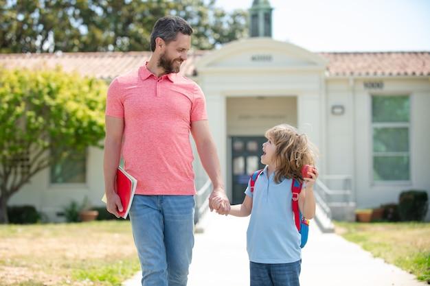 Ojciec i syn spacerują po szkolnym parku, ojciec i syn chodzą do szkoły, edukacji i nauki