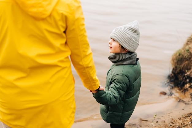 Ojciec i syn stoją nad brzegiem jeziora i trzymają się za ręce szczęśliwa rodzina z dzieckiem chłopiec bawi się