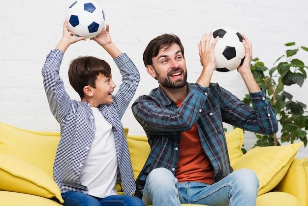 Ojciec i syn, trzymając piłki nożnej