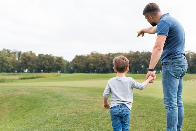 Ojciec i syn trzymając się za ręce od tyłu strzału