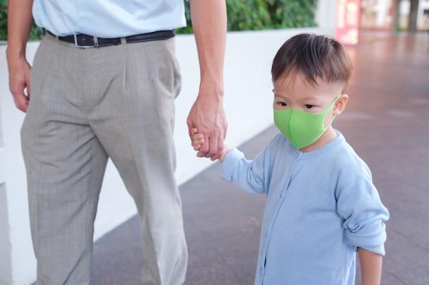 Ojciec i syn trzymający rękę, słodki mały azjatycki 2–3-letni maluch chłopiec dziecko noszące ochronną maskę medyczną, tata i syn stojący w miejscu publicznym (lotnisko / szpital / dom towarowy)