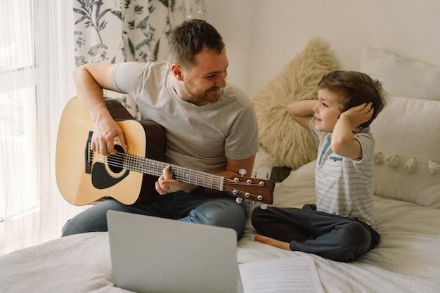 Ojciec i syn uczą się gry na gitarze akustycznej podczas lekcji online.