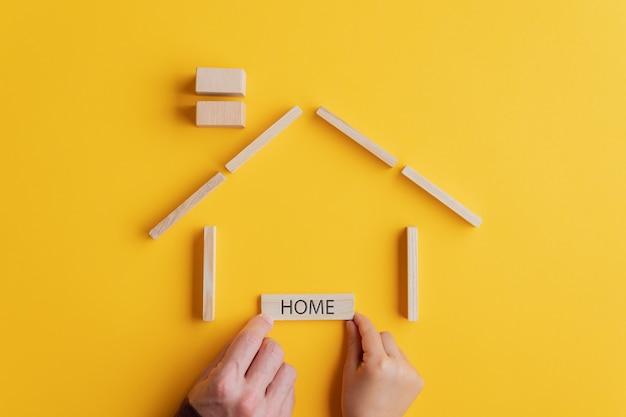 Ojciec i syn umieszczenie drewnianego znacznika home pod domem z kołków i bloków w koncepcyjnym obrazie.