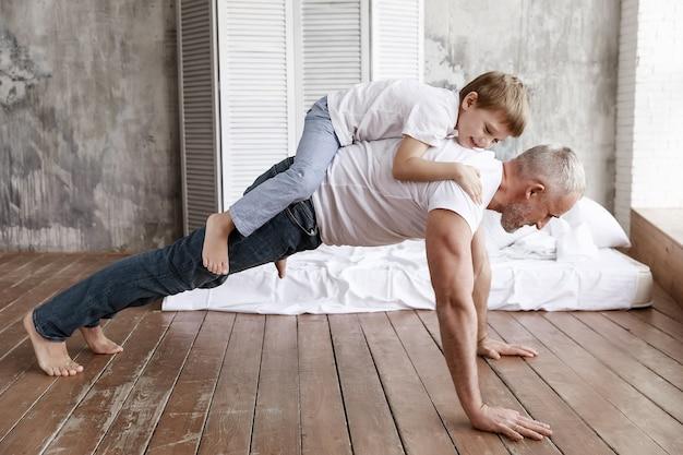 Ojciec i syn uprawiają sport w domu.