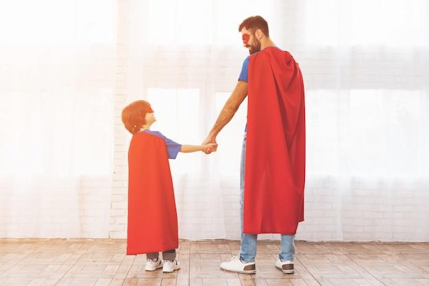 Ojciec i syn w czerwonych i niebieskich garniturach superbohaterów.