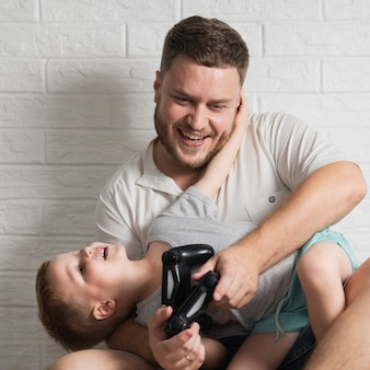 Ojciec i syn w domu, grając w gry cyfrowe