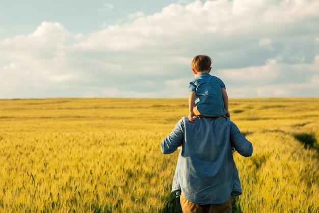 Ojciec i syn w polu pszenicy, dziecko siedzi na ramionach ojców