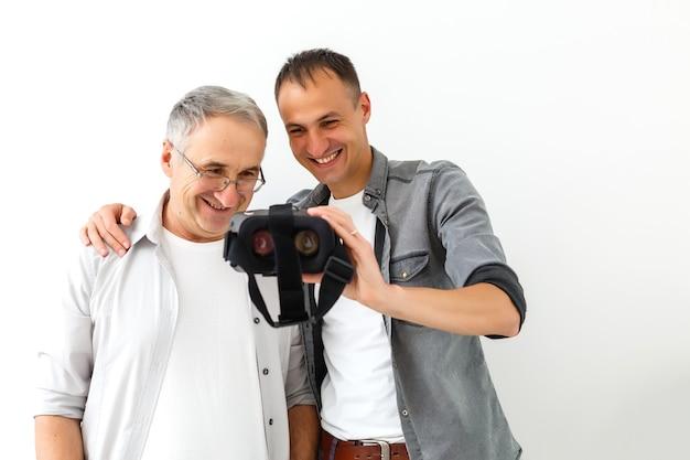 Ojciec i syn w wirtualnych okularach, na białym tle biała ściana.
