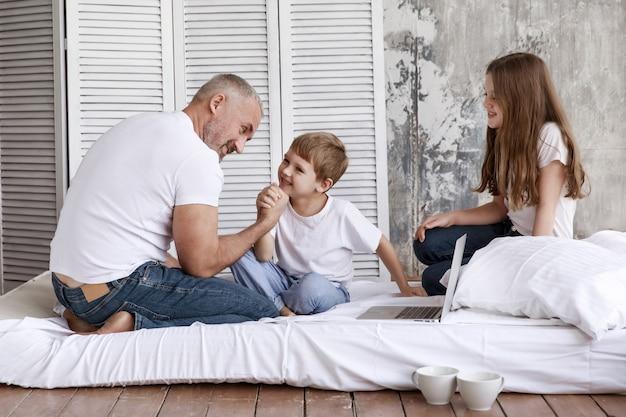 Ojciec i syn walczą w swoich ramionach, a jego córka ich obserwuje