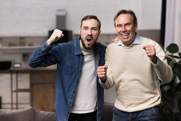 Ojciec i syn wiwatują w salonie
