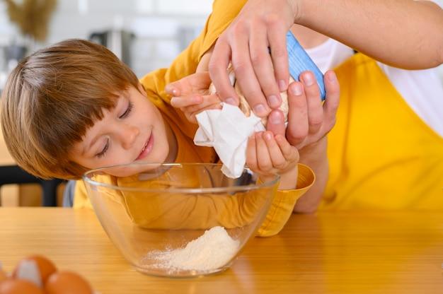 Ojciec i syn wlewają mąkę do miski