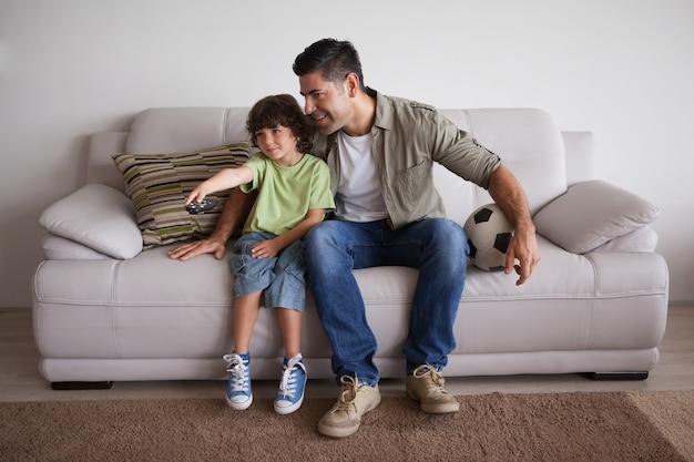 Ojciec i syn z futbolem oglądania telewizji w salonie