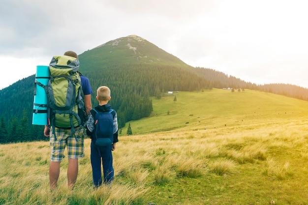Ojciec i syn z plecakami wędrówki razem w górach latem. tylny widok tata i dziecka mienia ręki na krajobrazowym widoku górskim. aktywny styl życia, relacje rodzinne, koncepcja aktywności weekendowej