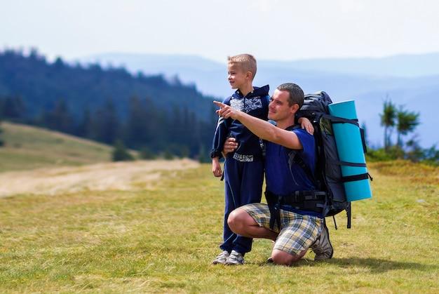 Ojciec i syn z plecakami wędruje razem w malowniczych letnich zielonych górach. tata i dziecko pozycja cieszy się krajobrazowego widok górskiego. aktywny styl życia, relacje rodzinne, aktywność weekendowa.