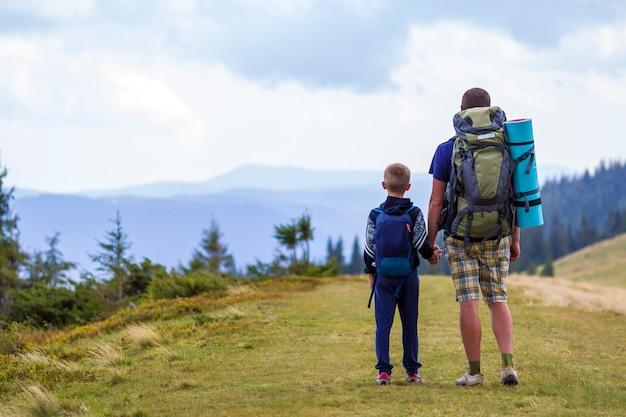 Ojciec i syn z plecakami wędruje razem w malowniczych letnich zielonych górach. tata i dziecko pozycja cieszy się krajobrazowego widok górskiego. aktywny styl życia, relacje rodzinne, koncepcja aktywności weekendowej.