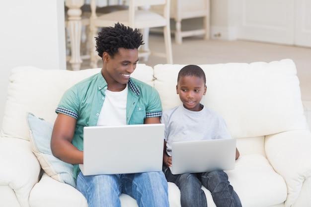 Ojciec i syn za pomocą laptopów na kanapie