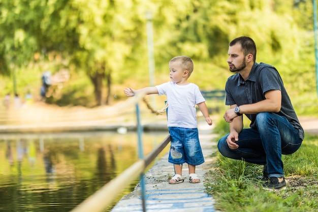 Ojciec i syn, zabawy w pobliżu jeziora w parku latem