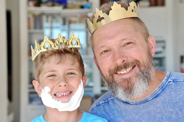 Ojciec i syn zakładają koronę na głowy i bawią się. ojciec ma brodę. syn zrobił brodę z pianki do golenia