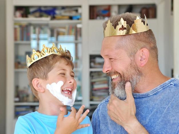 Ojciec i syn zakładają koronę na głowy i bawią się. syn zrobił brodę z pianki do golenia.